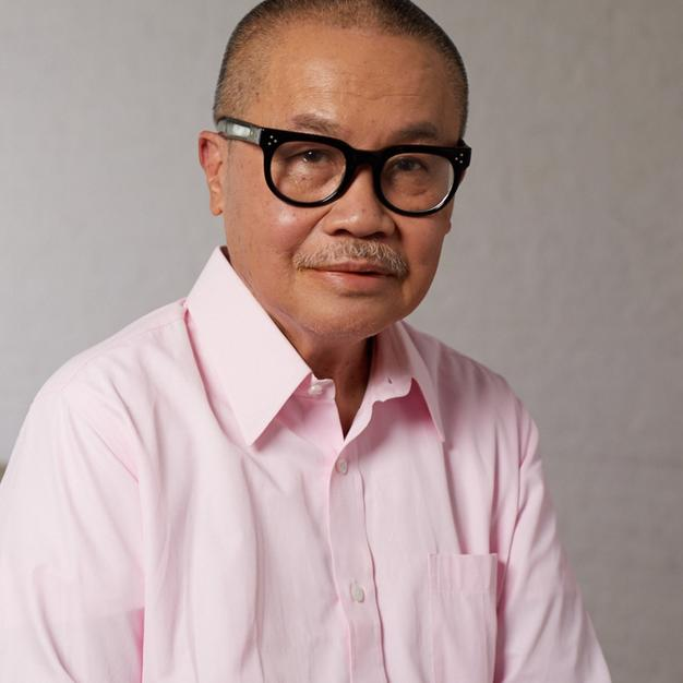 Older man wearing a pink button down and black rimmed glasses smiling for camera.