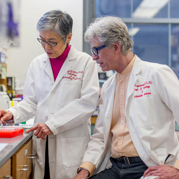 Male and female researcher wearing white lab coats chatting in the lab.