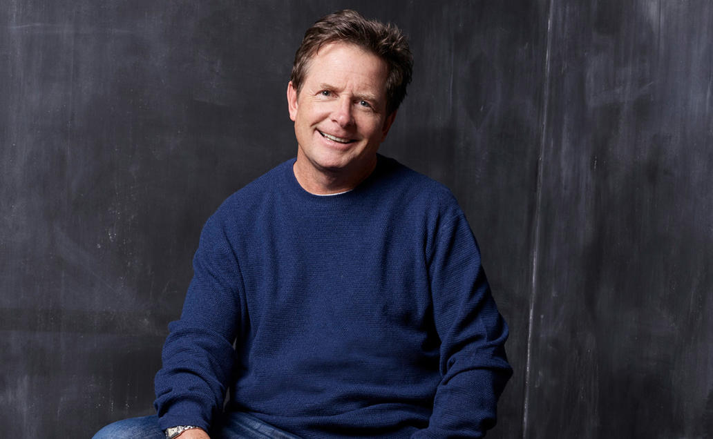 Michael J. Fox in blue sweater posing for the camera.