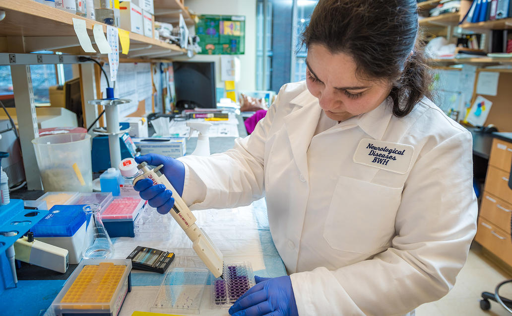 Female researcher pipetting in lab.