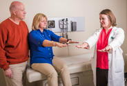 Male care partner alongside female patient undergoing Parkinson's test with her female physician.