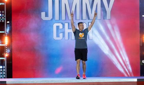 Jimmy Choi with his hands in the air cheering, while walking on to the American Ninja Warrior course.