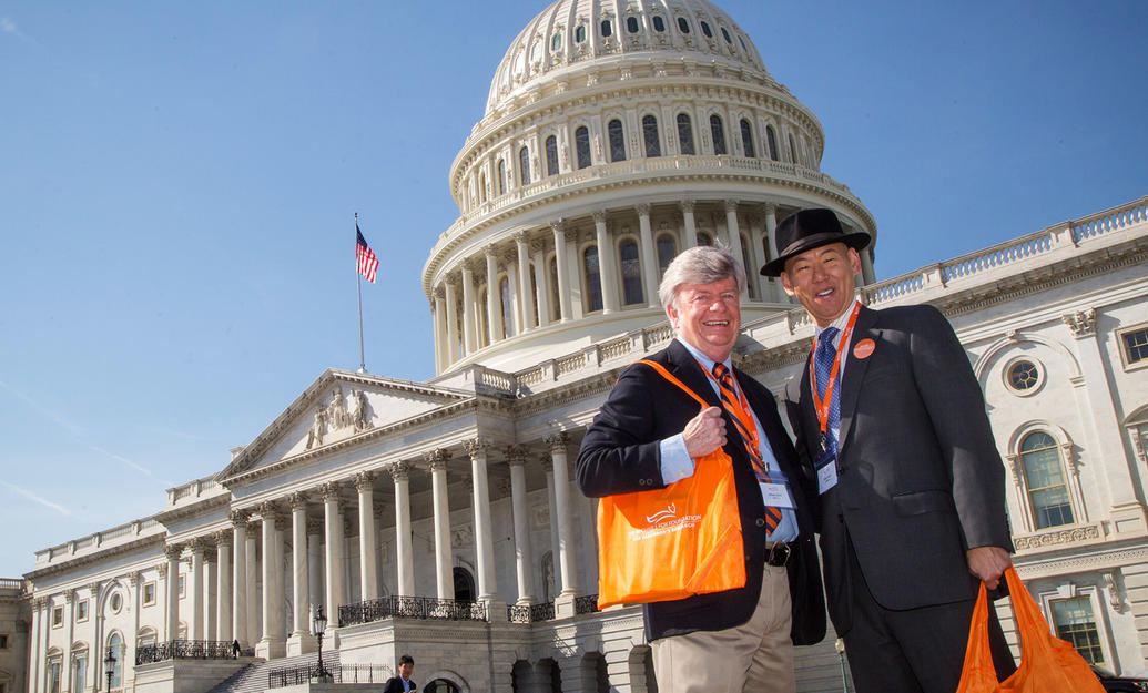 Two male advocates in front of the United States Capitol building at the Parkinson's Policy Forum.