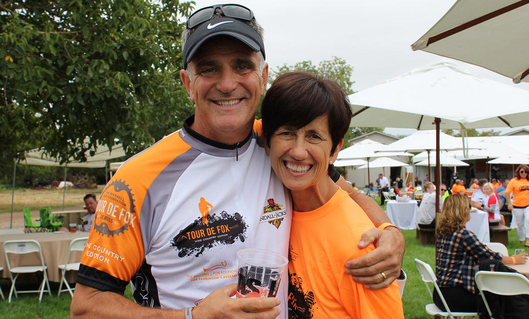 Male and female couple smiling for the camera at a Tour de Fox cycling event.