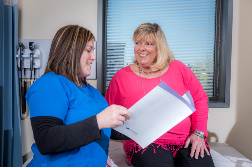 Female nurse and woman with Parkinson's in the doctor's office looking over a pamphlet.