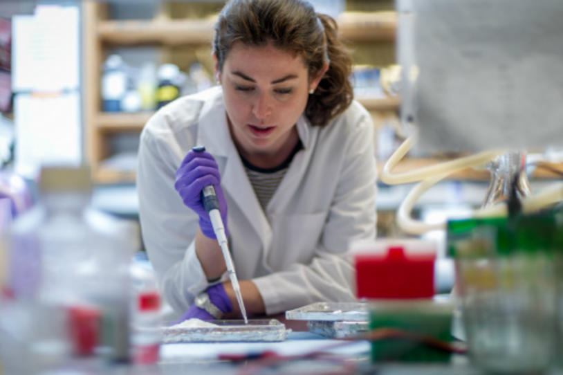 Female researcher pipetting in the lab.