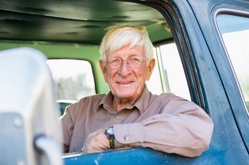 Older man sitting in the front seat of his truck.