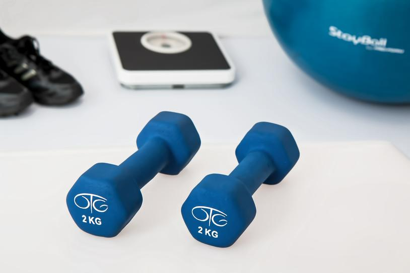 Set of weights next to blacks sneakers, a scale and blue ball.