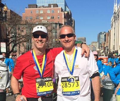 Two male runners posing for the camera at the Boston marathon.
