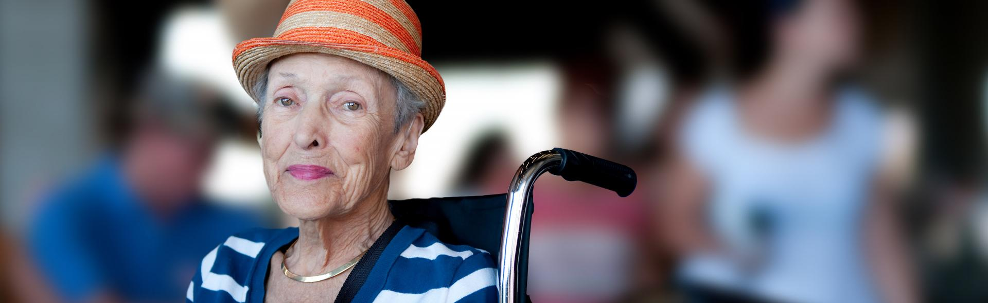 Older white woman wearing an orange striped fedora and blue and white striped shirt sitting in a wheelchair.
