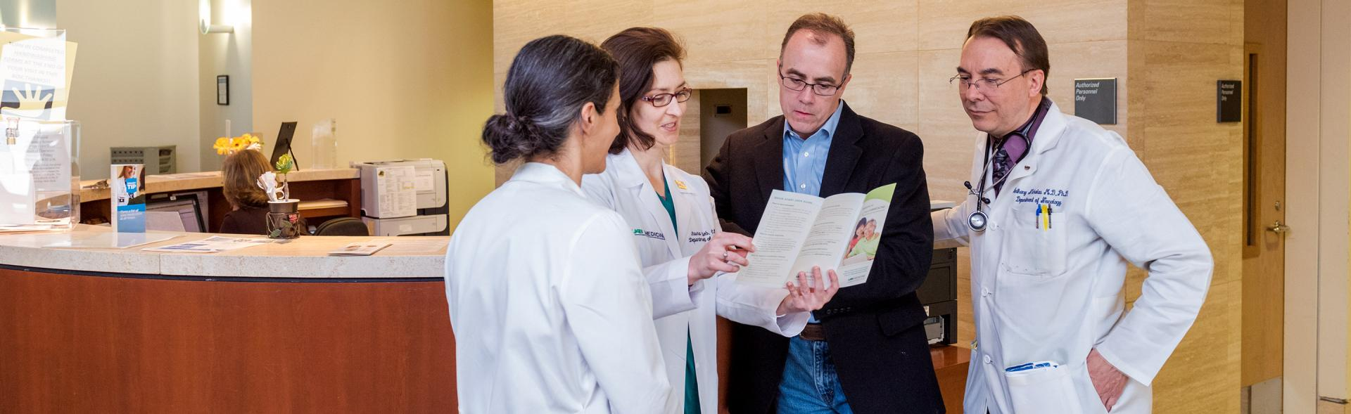 Male patient in doctor's office standing with three doctors looking at a brochure.