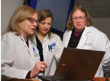 Three Caucasian female doctors looking at a laptop.